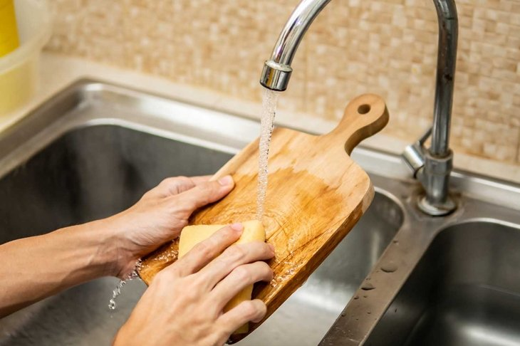 Cleaning wood cutting board in kitchen sink