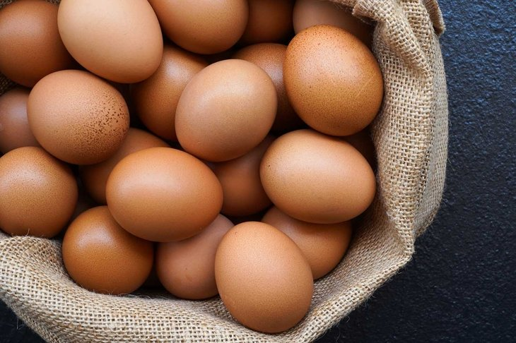 Chicken eggs in sack bag on black background.