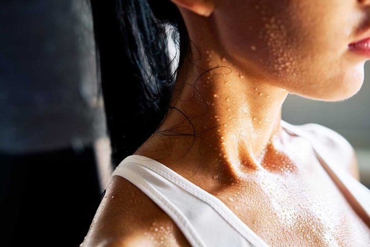 Close up shoulders and neck of a beautiful sporty girl in drop of sweat on skin after workout