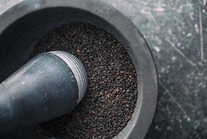Black sesame seeds. Healthy sesame seeds in mortar. Top view.