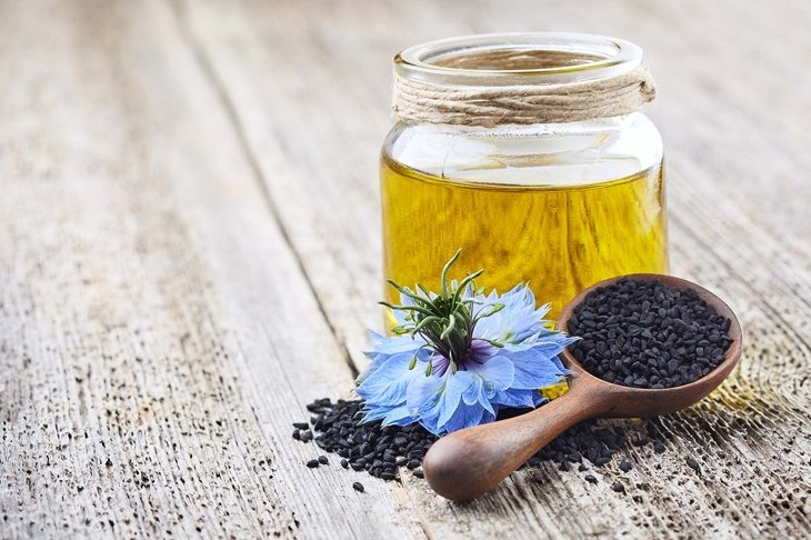 Black cumin oil with flower nigella sativa on wooden board