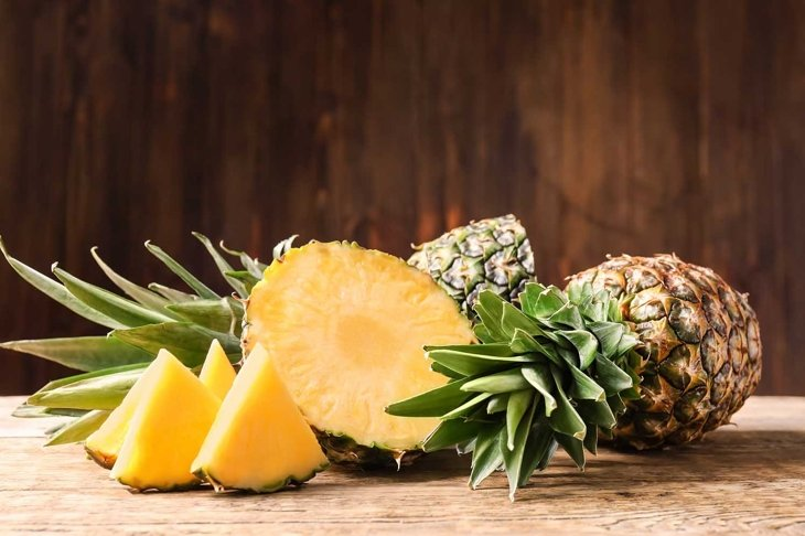 Whole and cut ripe pineapples on wooden table