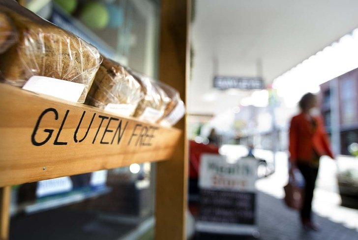 AUCKLAND, NZ - OCT 09 2013:Woman passing by Gluten free bakery. Gluten-free food is normally seen as a diet for celiac disease, nearly 1 out of every 133 people has celiac disease.