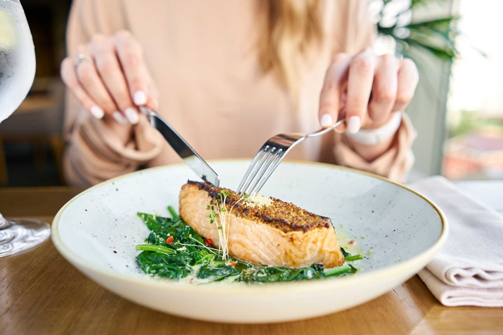 Salmon steak fillet with grainy mustard and spinach. Lunch in a restaurant, a woman eats delicious and healthy food. Restaurant menu, a series of photos of different dishes
