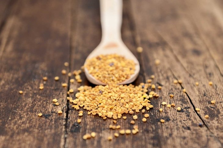 spoon with seeds isolated on pollen focus on rustic background