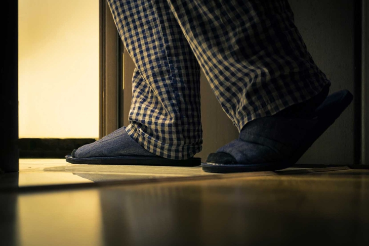 Adult man in pajamas walks to a bathroom at the night. Men's healths concept
