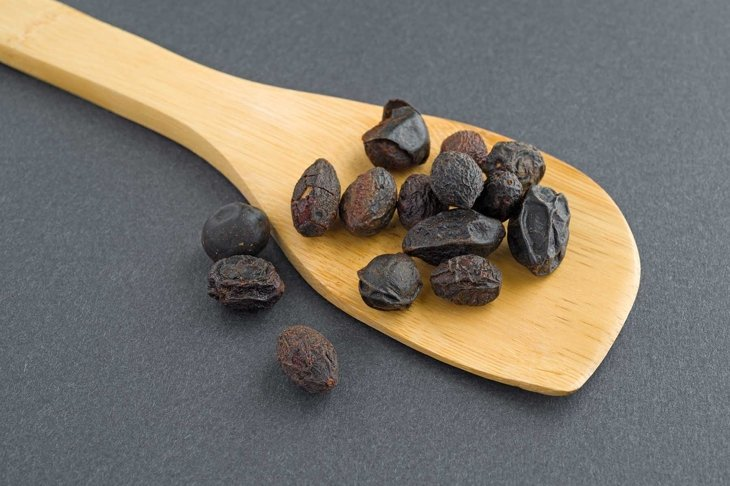 A wood spoon with saw palmetto berries on a dark background.