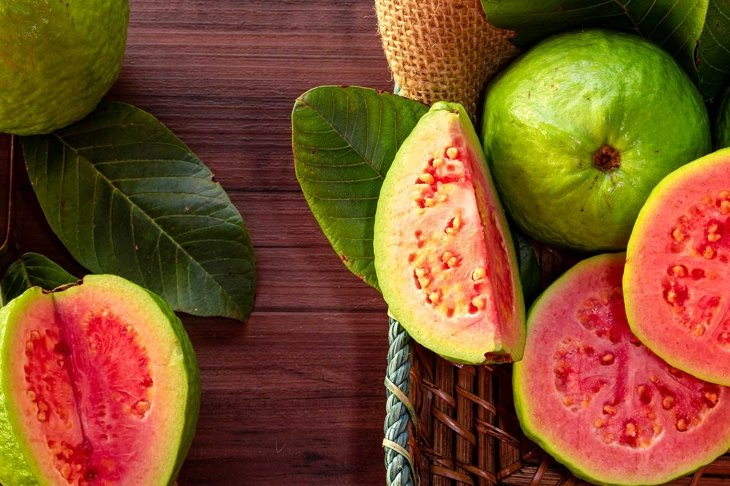 Closeup of a red guava cut in half, in the background several guavas and green leaf