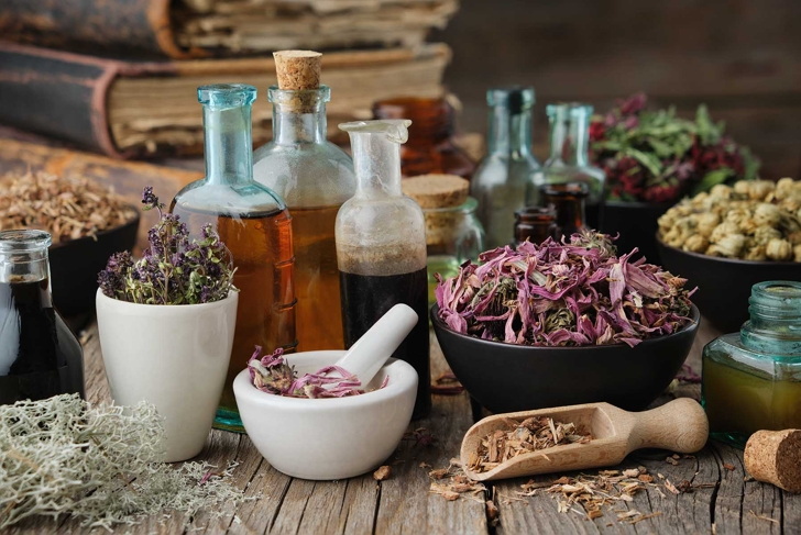 Bottles of healthy tincture or infusion, mortar and bowls of medicinal herbs, old books on wooden table. Herbal medicine.
